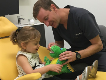 Dr. Bright giving a little girl a stuffed dinosaur to play with during her appointment