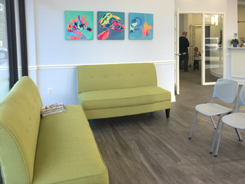 Green couches and colorful paintings hanging in the Bright Smiles' lobby