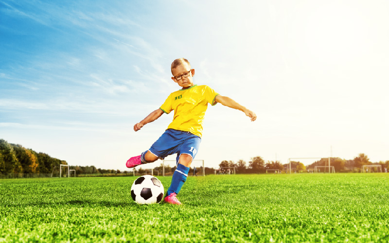 young boy kicking soccer ball outside