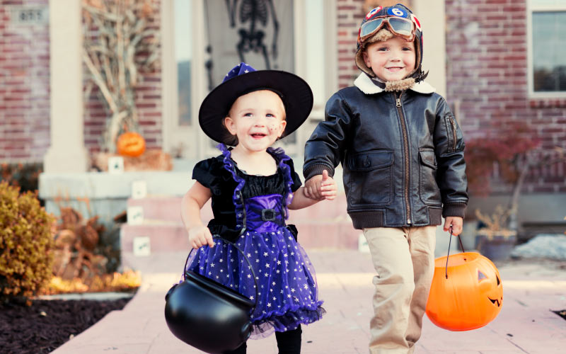 young girl and boy in costumes for halloween