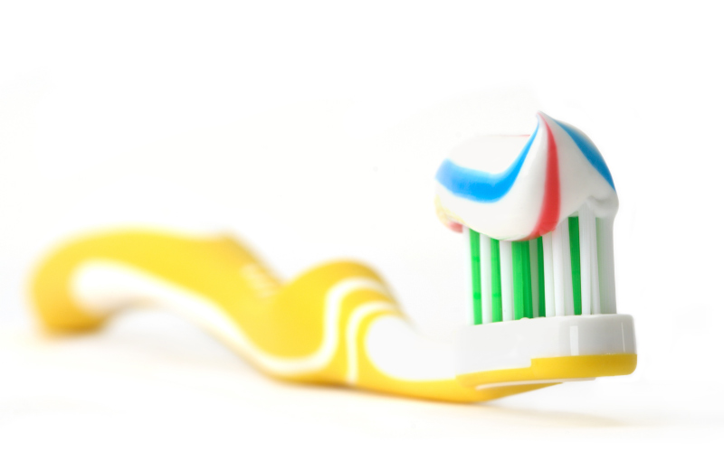 yellow toothbrush with blue red and white striped toothpaste sitting on white counter