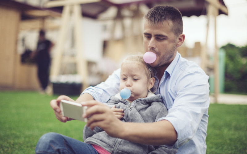Father and young daughter outside blowing bubbles with chewing gum and taking a picture.