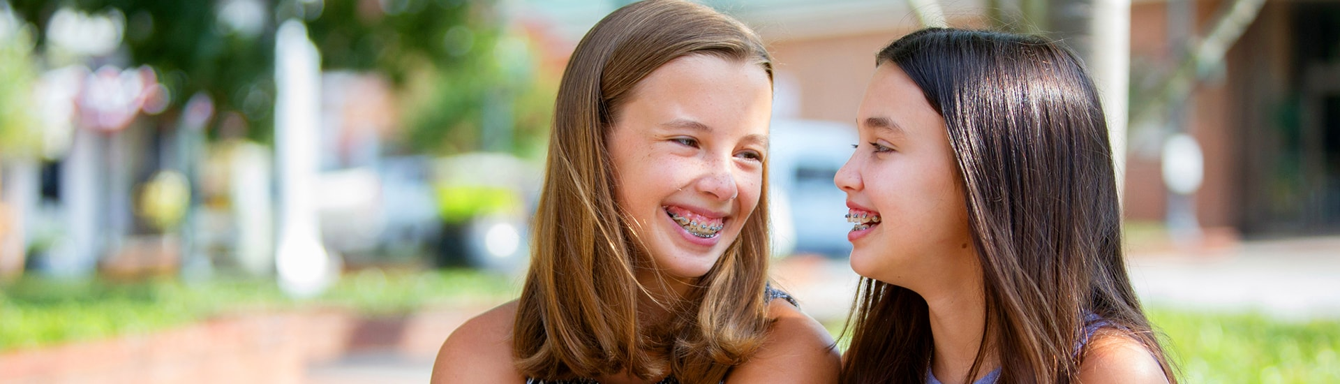 young blonde girl with braces and young brunette girl with braces, smiling and laughing outside
