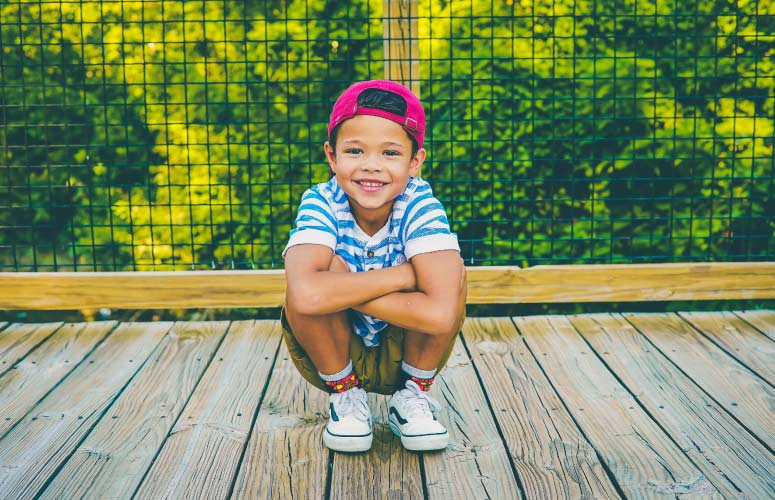 Young boy crouches on a wooden boardwalk before a wire railing wearing a red cap, blue striped shirt, and sneakers